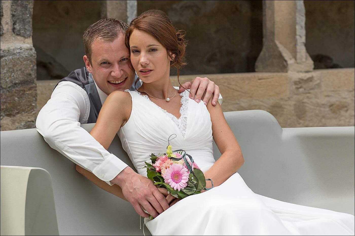 La mariée est assise sur un banc et le marié est accroupi derrière elle