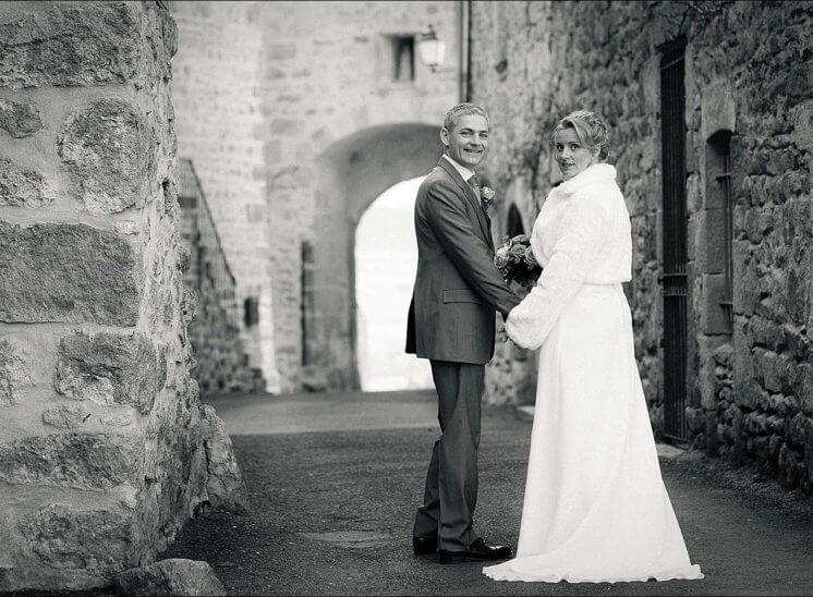 Deux mariés se tiennent par la main dans les rues de Montpeyroux
