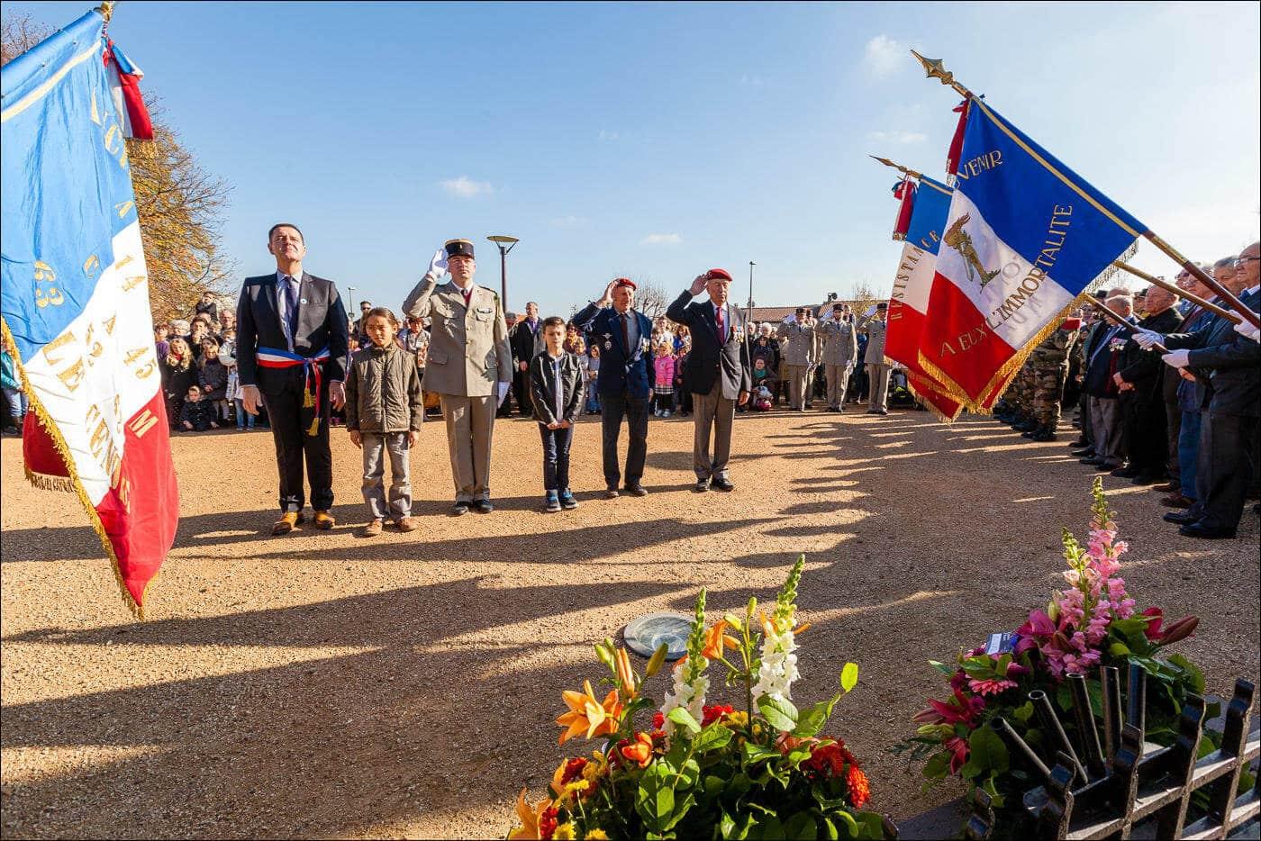 Un groupe composé du maire et de deux enfants, ainsi que d'un militaire et deux anciens combattants saluent lors de la commémoration devant le monument aux morts