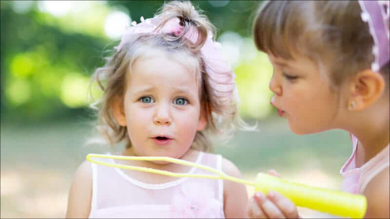 Deux soeurs jouent à faire des bulles de savon, la plus jeune souffle en regardant le photographe