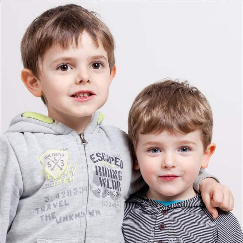 Deux frères très complices se tiennent par l'épaule et posent naturellement pour la photographie