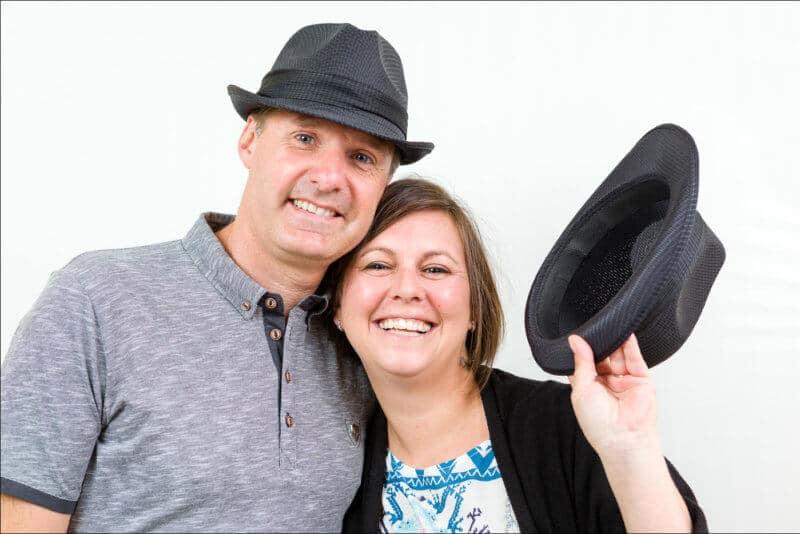 Un couple joue avec des chapeaux. Ils posent naturellement lors d'une séance de shooting photo.
