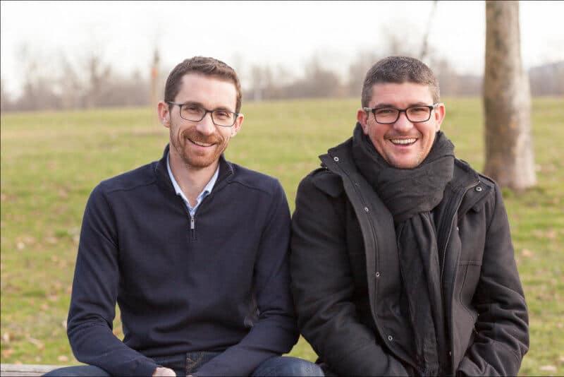 Deux frères assis sur un banc rigolent devant le photographe