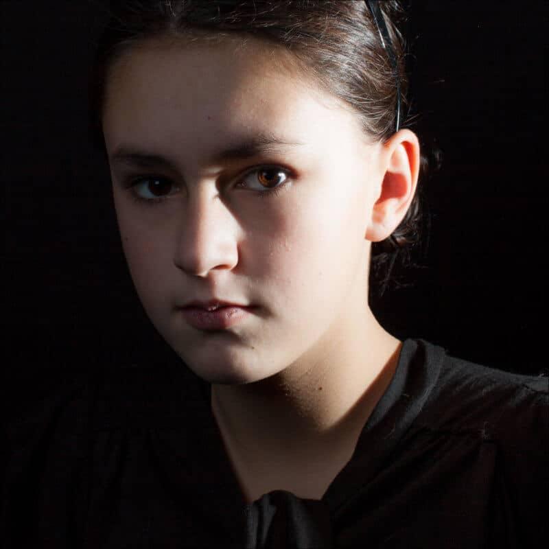 Une jeune fille habillée en noir regarde fixement l'objectif lors d'une séance de photo studio