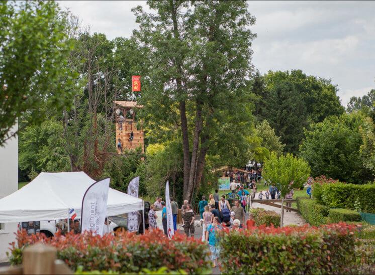 Des jeux en plein air sont installés dans un parc. L'un d'eux dépasse de la cime des arbres et une tente est visible au premier plan. Il y a beaucoup de monde dans le chemin