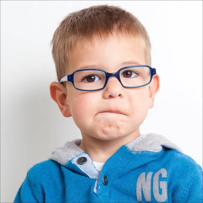 Un enfant fait une très jolie grimace. Il a un très jolie visage