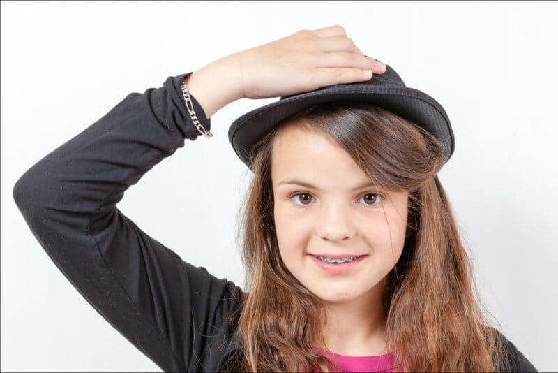 Une jeune fille a saisit le chapeau sur sa tête pour le retirer