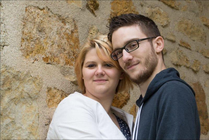 Deux amoureux posent tête contre tête devant un mur en pierre.
