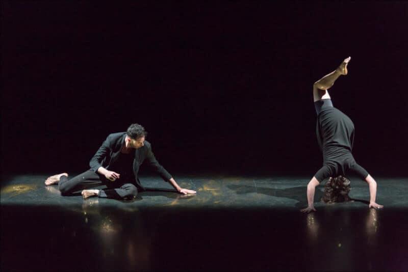 Deux personnes en tenue sombre dancent sur une scène