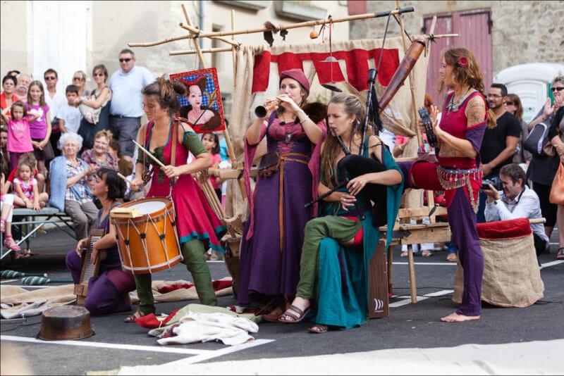 Cinq femmes habillées en style médiéval jouent de différents instruments de musique