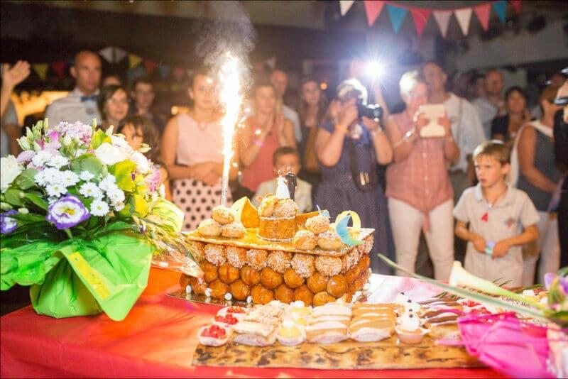 Le gateau des mariés, surmonté d'un feux, trône devant les invités du mariage
