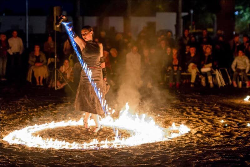 La danseuse de tango déverse de l'essence en flamme , formant un cercle de feu autour d'elle.