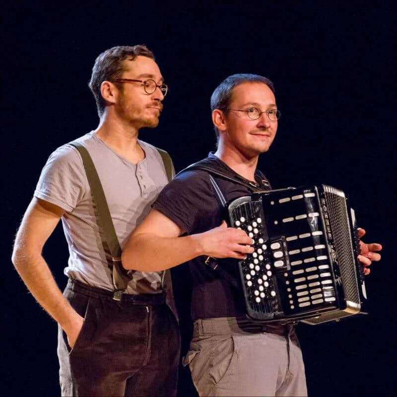 Un pesonnage joue de l'accordéon en regardant le public. Le second est derrière lui avec les mains dans les poches.