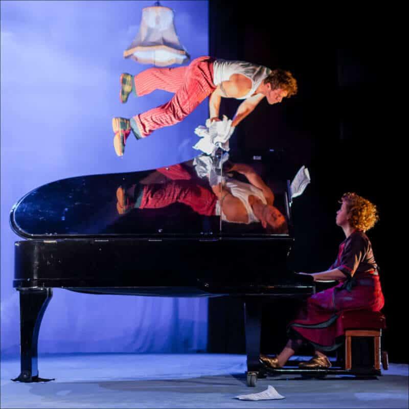 Un homme fait un équilibre sur un piano alors qu'une femme est en train de jouer