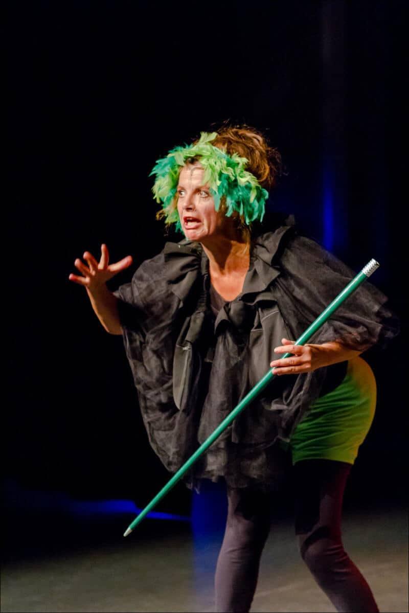 L'interprète de ce spectacle tient une canne verte dans la main et interpelle le public