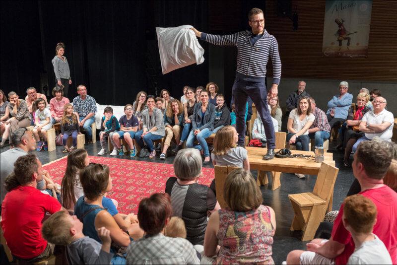 Un homme qui interprète un spectacle, se tient debout sur une table avec un oreiller dans la main