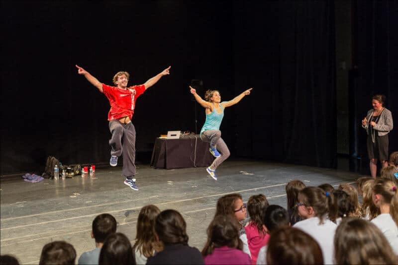 Deux danseurs de hip hop sautent en levant les bras.