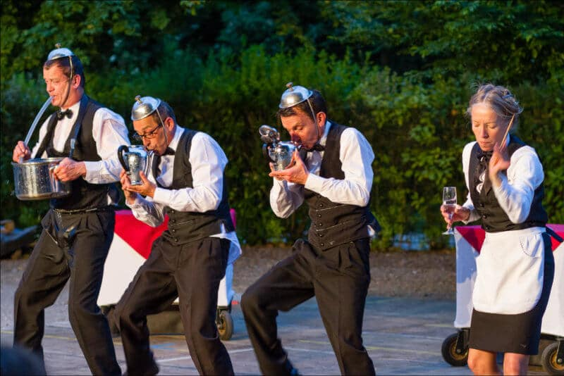 Quatres comédiens déguisés en serveurs de café jouent de la musique avec des ustensiles de cuisine