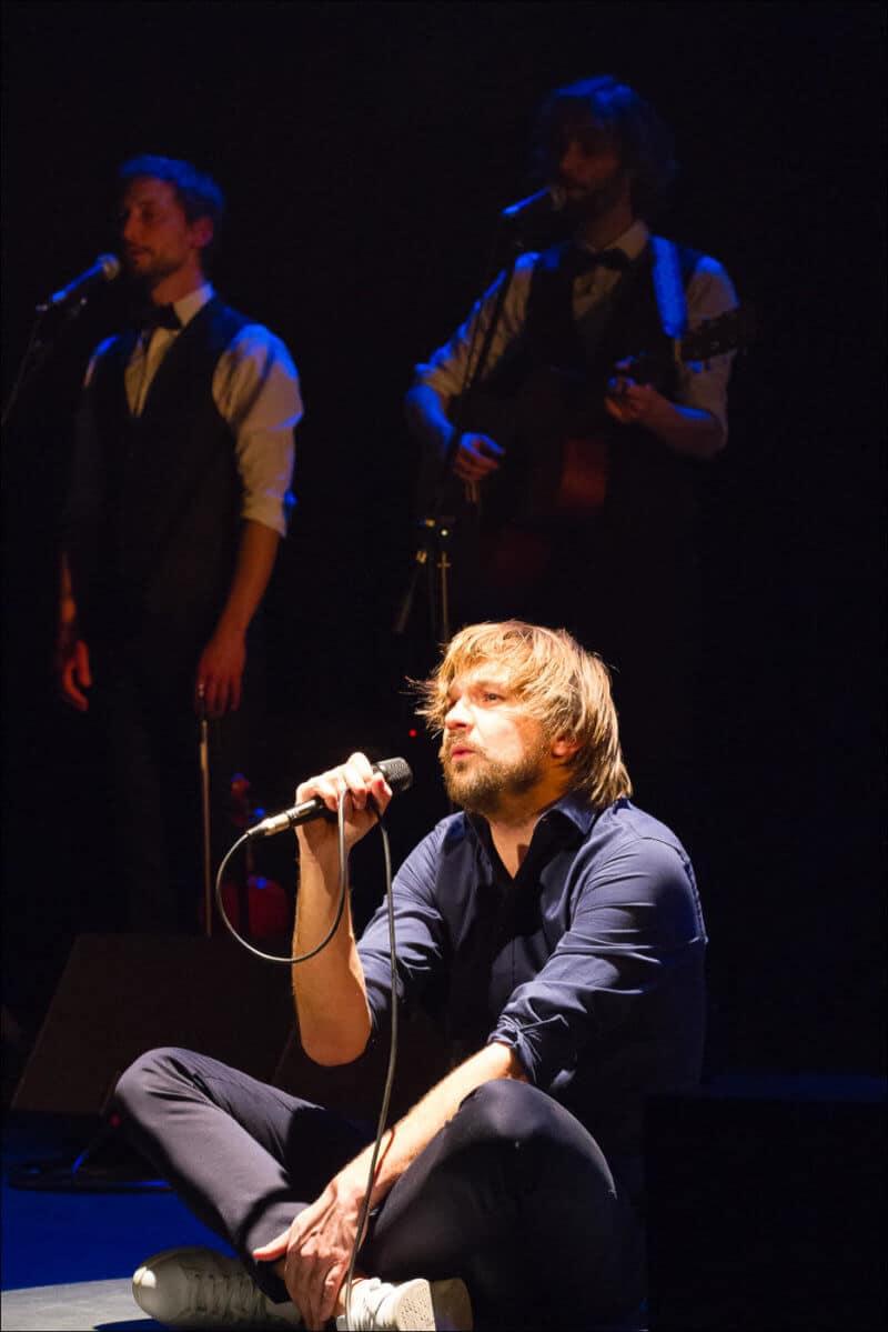 Le chanteur du groupe est assis sur la scéne, en pleine lumière, alors que deux musiciens sont derrière lui, dans l'ombre