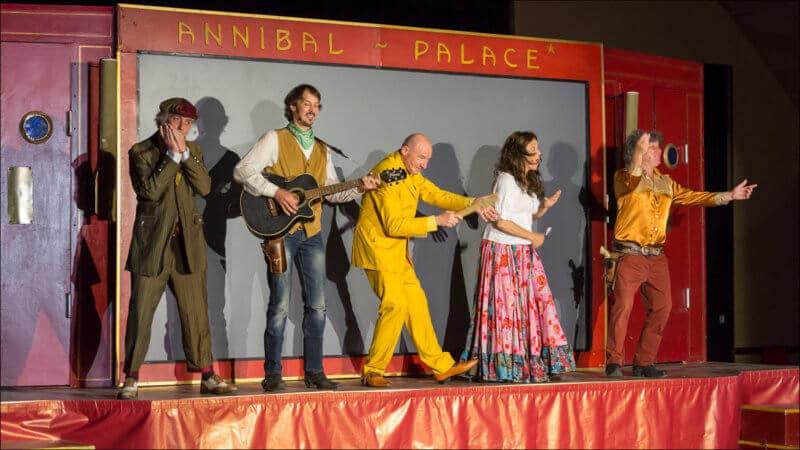 Les cinq memebres de la troupe se trouvent sur la scéne, devant un écran de cinéma