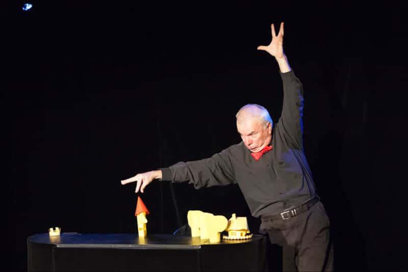 L'homme manipule des objets en papier de la main droite alors qu'il a sont bras gauche levé.