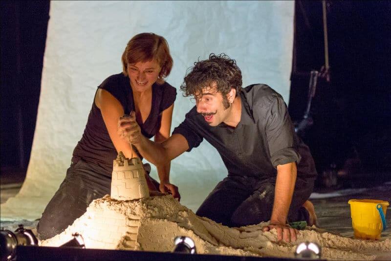 Deux artistes construisent un chateau de sable. L'homme laisse couler le sable qu'il a dans sa main.