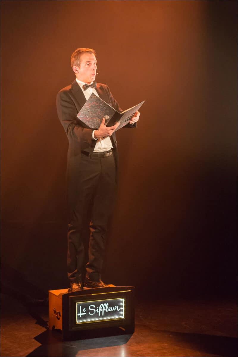 L'artiste se tient debout sur un caisson et tient en main une partition qu'il exécute en sifflant