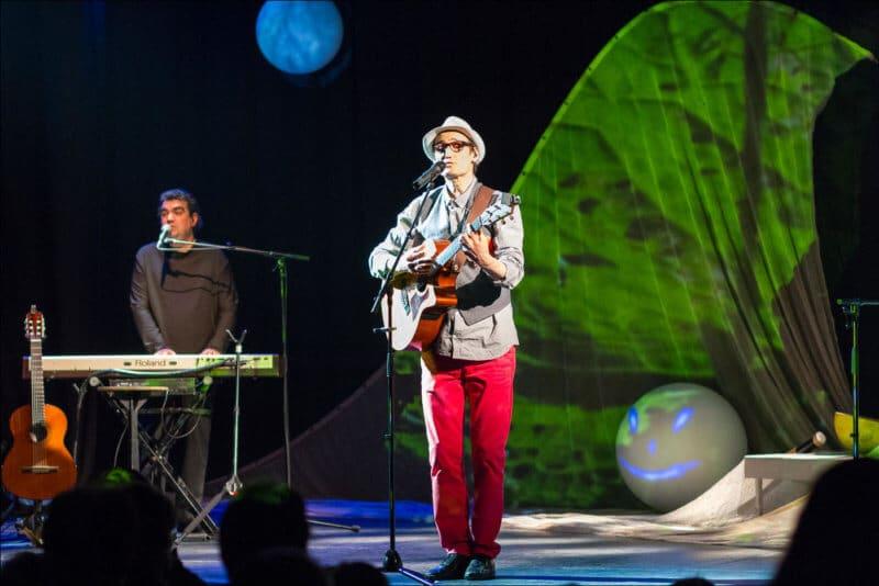 Un guitariste et un pianiste jouent sur scène devant un décor enfantin