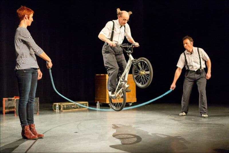 Deux personnes font tourner une corde à sauter alors qu'un autre artiste saute par dessus avec un vélo