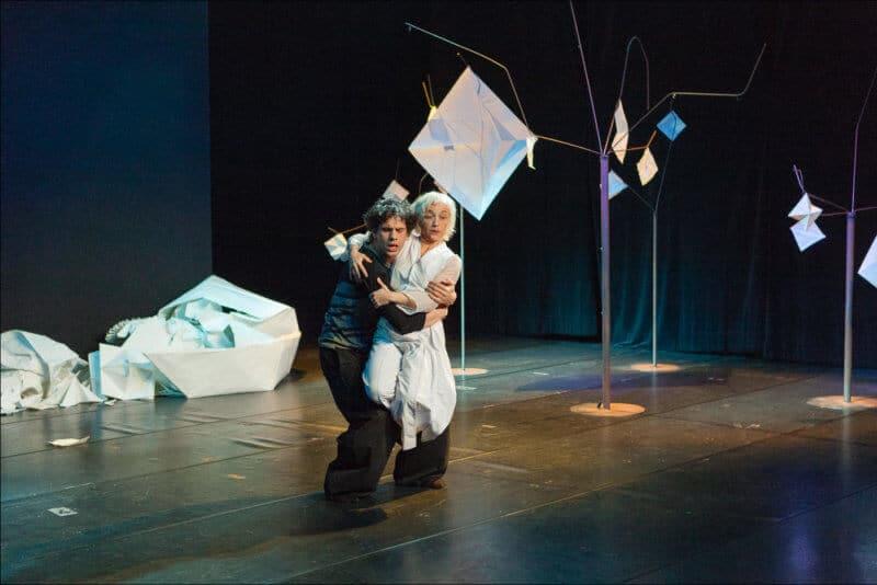 Parmi une scène remplie de papiers posés au sol, les deux danseurs exécutent leur ballet avec grace