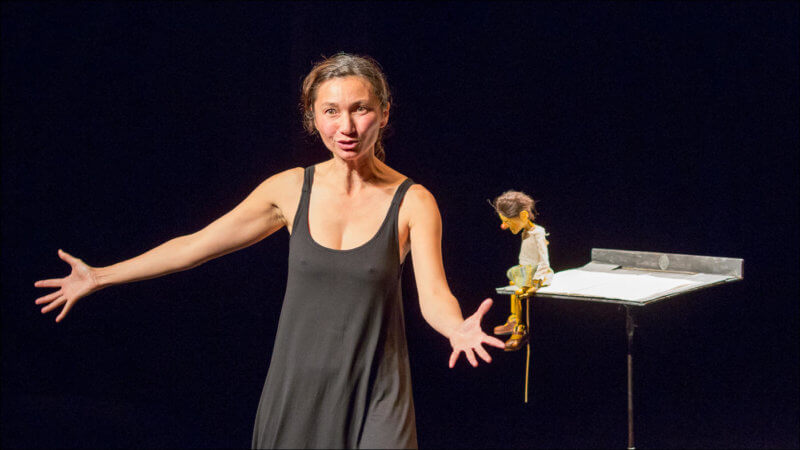 L'actrice est face au public avec les mains et les bras ouvert, alors sa marionnette est posée sur un pupitre à côté d'elle