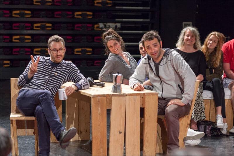 Les trois artistes sont assis autour d'une table en bois. L'un d'eux fait un signe de V avec ses doigts