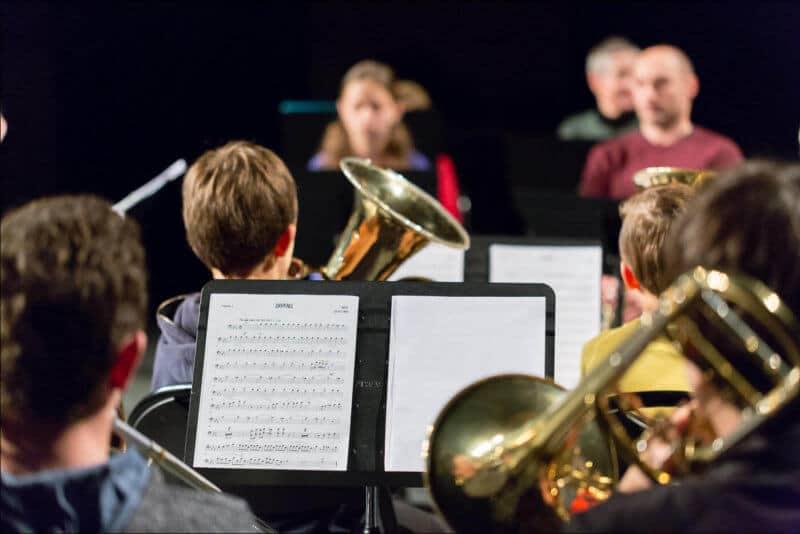 Lors d'un concert d'une école de musique, les jeunes élèves sont de dos avec leurs instruments. La partition est sur le pupitre