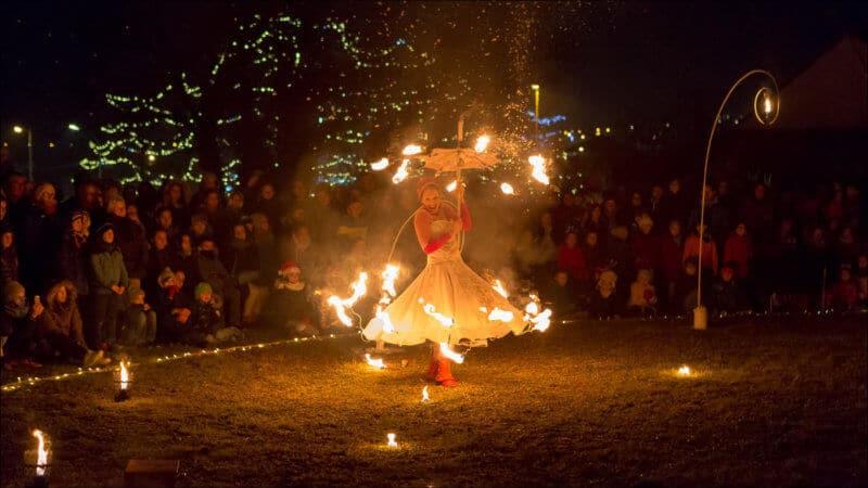 L'artiste de ce spectacle se déplace avec une robe et un parapluie sur lesquels sont fixés des petites flammes. Le public est rassemblé autour de la scéne