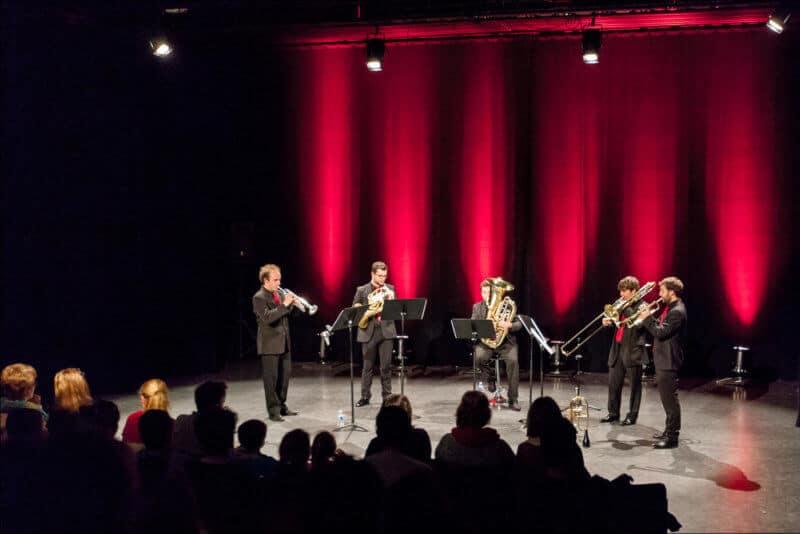 Un groupe de cinq musiciens se produit sur une scéne éclairée de lumière rouge