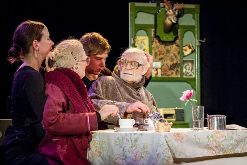 Un spectacle de marionnette à taille humaine où les deux personnes prennent le thé devant une table