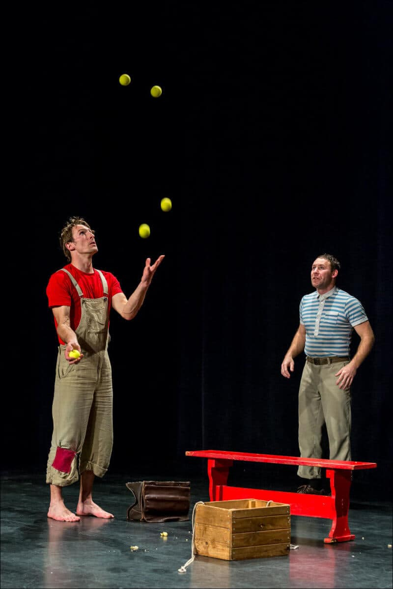 Un artiste jongle avec cinq balles alors que l'autre le reagarde