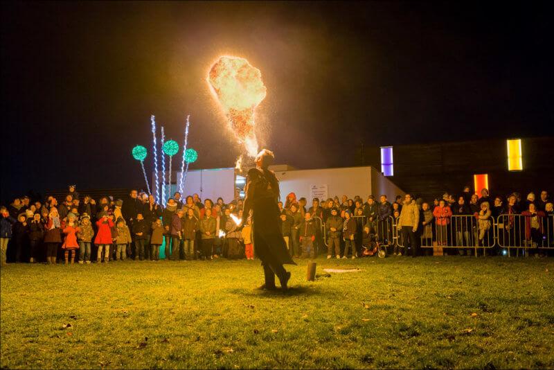 La foule encercle un craqueur de feu qui souffle dans flammes dans la nuit, devant la salle LES JUSTES au CENDRE