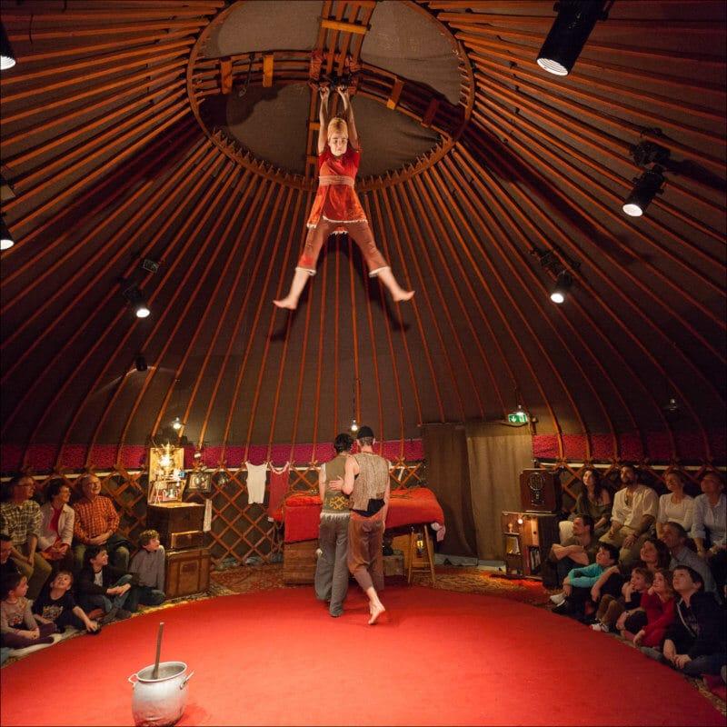 A l'intérieur d'un yourte, une femme est accrochée au plafond alors que deux homme discutement au dessous. Le public de ce spectacle est assis tout autour de la scène