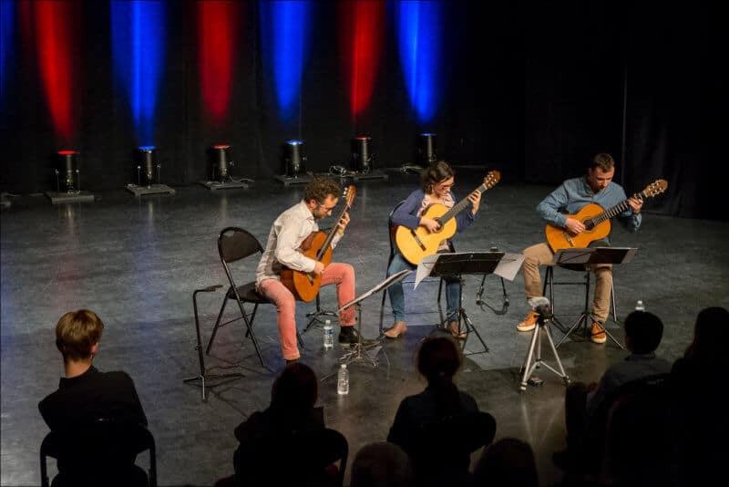 Les trois musiciens du Trio Explora jouent de la guitare sur la scène de la salle LES JUSTES
