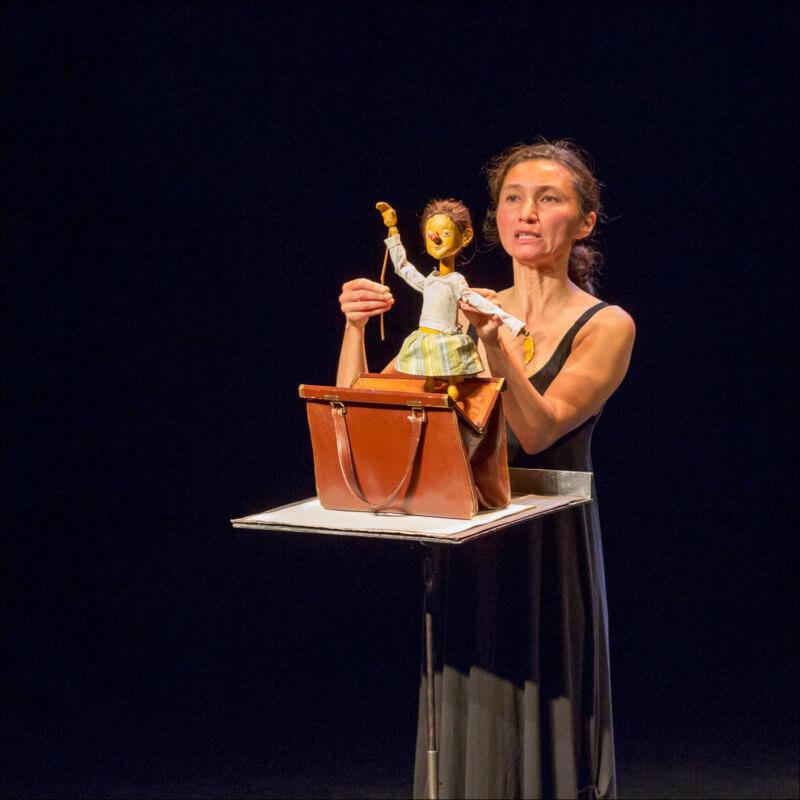 Une marionnettiste sort d'un sac posé sur un pupitre, une petite poupée qui salue le public