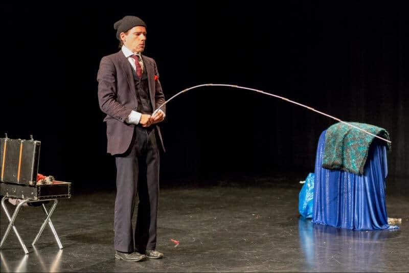 L'ariste de ce spectacle, vêtu d'un costume et d'un bonnet, tient un mètre pliant devant lui pour représenter qu'il urine
