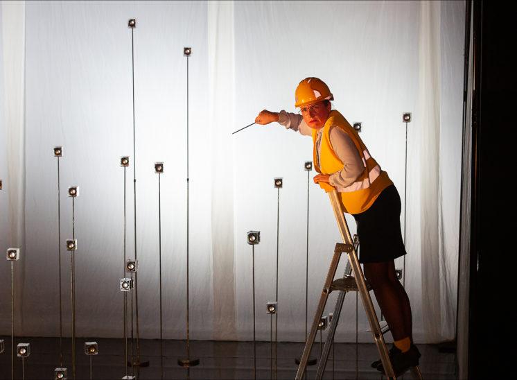 Une erpsonne le trouve debout sur un escabeau et fait le chef d'orchestre face àdes boite inter-actives
