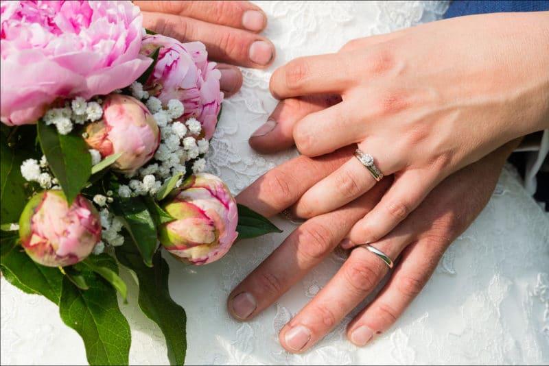 Gros plan des mains des mariés avec le bouquet