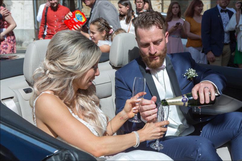 Les mariés boivent une coupe de champagne dans la voiture cabriolet