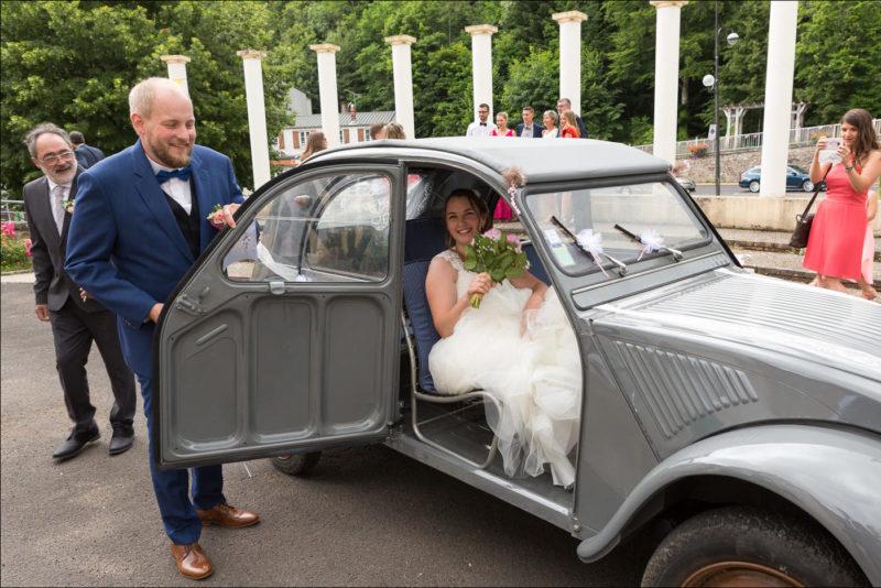 Le marié tient la porte de la 2cv ou se trouve la mariée