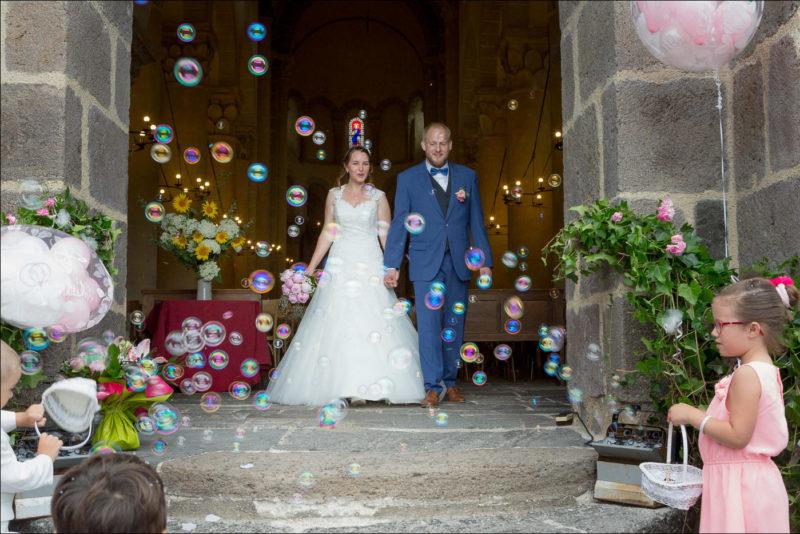 Les enfants font des bulles de savon et les mariès sortent de l'église