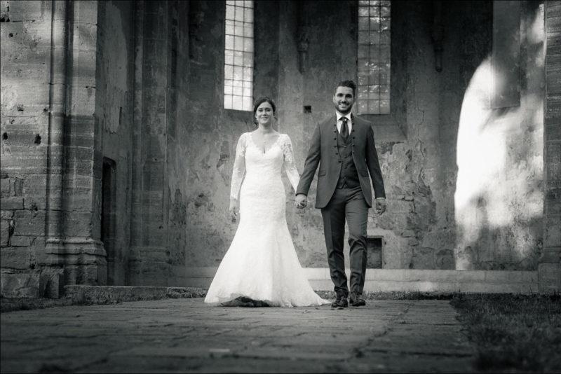 Les mariés se tiennent par la main et avancent vers le photographe