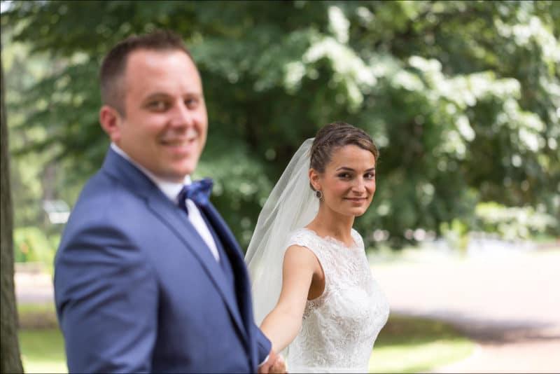 La mariée tire le bras du marié en premier plan flou
