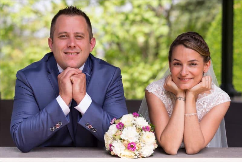Les mariés posent lors des photos de couple, de chaque côté du bouquet